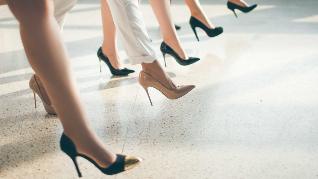 mulheres sentadas com o close nos sapatos